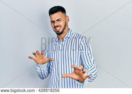 Young hispanic man with beard wearing casual striped shirt disgusted expression, displeased and fearful doing disgust face because aversion reaction. with hands raised
