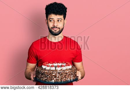 Young arab man with beard celebrating birthday holding big chocolate cake smiling looking to the side and staring away thinking.