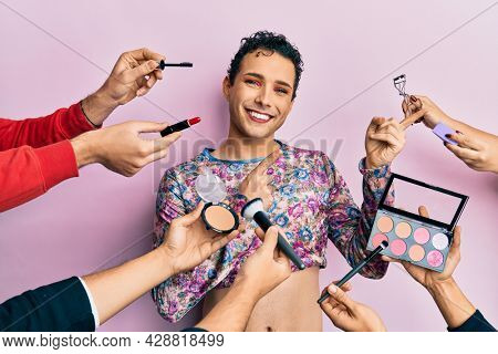 Handsome man wearing make up with make up cosmetics around smiling and looking at the camera pointing with two hands and fingers to the side.