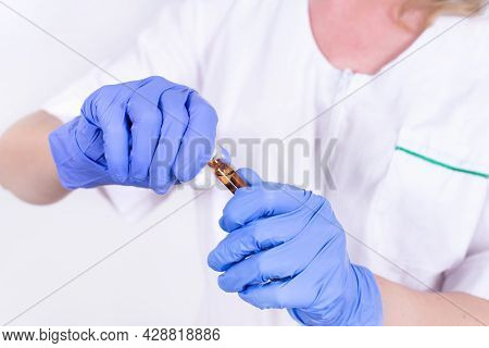 Female Doctor Or Nurse In A Protective Mask And Gloves Opens An Ampoule With A Vaccine For Injection