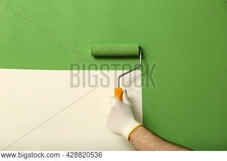 Man Applying Green Paint With Roller Brush On White Wall, Closeup
