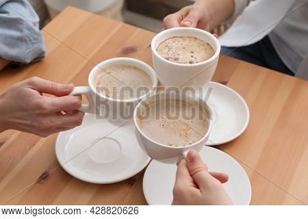Women Clinking Cups Of Coffee At Table In Cafe, Closeup