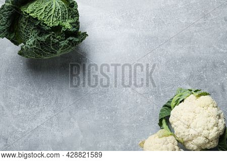 Fresh Ripe Savoy Cabbage And Cauliflower On Grey Table, Flat Lay. Space For Text