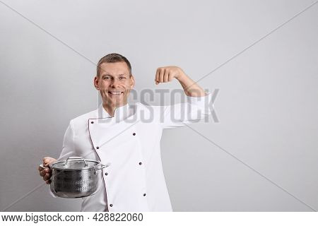 Happy Male Chef With Cooking Pot On Light Grey Background. Space For Text