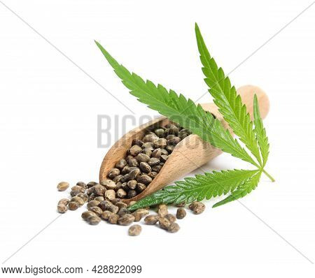 Wooden Scoop With Hemp Seeds And Leaf On White Background