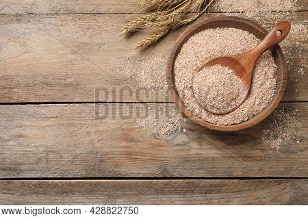 Wheat Bran And Spoon In Bowl On Wooden Table, Flat Lay. Space For Text