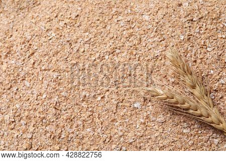 Spikelets On Heap Of Wheat Bran, Flat Lay. Space For Text