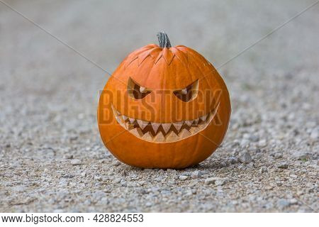 Scary Smiling Halloween Pumpkin With Nasty Face On Ground. Big Scary Smiling Halloween Pumpkin With