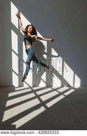 Asian dancer girl makes an acrobatic jump illuminated by the sun that enters through the window in an empty building. isolated