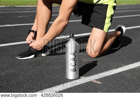 Bottle With Amino Acids (bcaa) Drink And Young Man Tying Shoelaces At Stadium