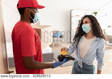 Black Deliveryman Holding Nfc Terminal Lady Paying With Bankcard