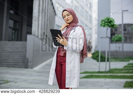 Portrait Of Beautiful Young Arabian Woman Doctor Holding Digital Tablet And Looking At Camera. Confi