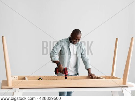 Carpentry Service. Black Handyman Drilling Wooden Planks Of Table Over Light Wall, Free Space