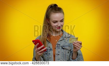 Sincere Teen Student Girl 20s Years Old In Denim Jacket Using Credit Bank Card And Smartphone While