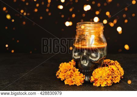 Burning Candle Skull With Marigold Flowers And Bokeh Lights On Black Background. Dia De Los Muertos