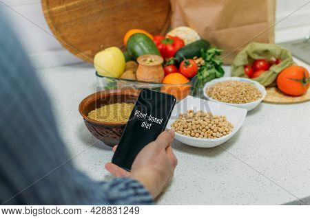 Whole-food, Plant-based Diet For Boost Health. Female Hand Cell Phone With Plant-based Menu Recipes