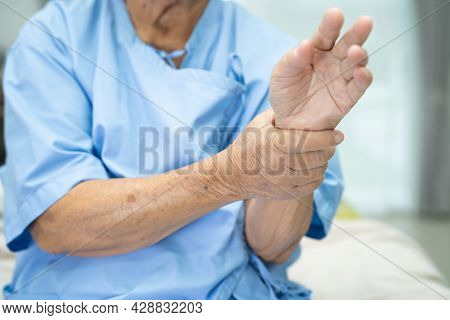 Asian Senior Or Elderly Old Lady Woman Patient Feel Pain Her Wrist And Hand On Bed In Nursing Hospit