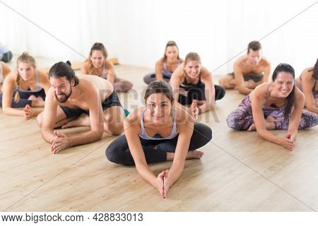 Group Of Young Sporty Attractive People In Yoga Studio, Practicing Yoga Lesson With Instructor, Sitt