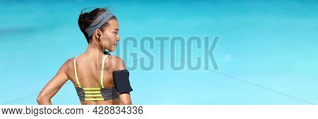 Wireless earphones and mobile phone music app for runner athlete running Asian woman listening to music podcast with earbuds wearing armband sleeve on beach run workout. Healthy fitness girl banner.