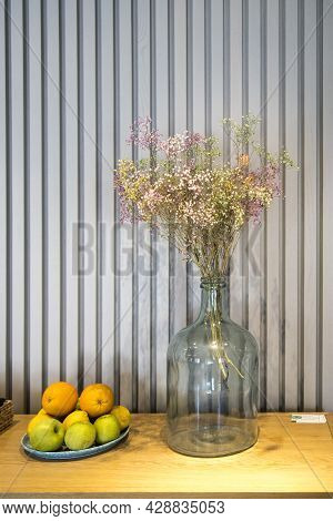 A Bouquet Of Multi-colored Painted Dried Gypsophila In A Large Glass Bottle Instead Of A Vase As A T
