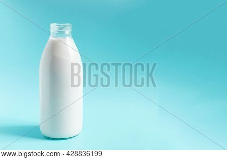 A Glass Bottle With Milk On A Blue Background. A Liter Of Milk In A Glass Bottle On A Colored Backgr