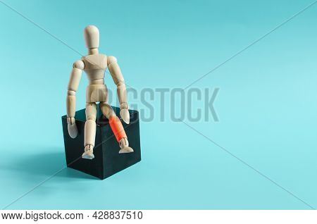 The Figure Of A Wooden Man Sitting On A Dark Podium. The Figure Of A Wooden Man With A Red Leg On A