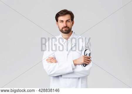 Hospital, Healthcare Workers, Covid-19 Treatment Concept. Handsome Confident Doctor In White Scrubs,