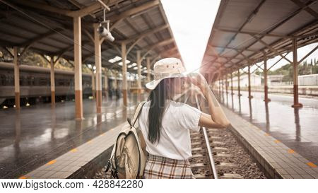 Young Female Tourist Good Feeling With A Backpack And Holding Her Hat On The Railroad Tracks At The