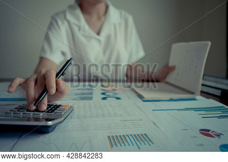 Close Up Businesswoman Hand Holding Pen Using A Calculator And Reading Note Book On Table Office. St