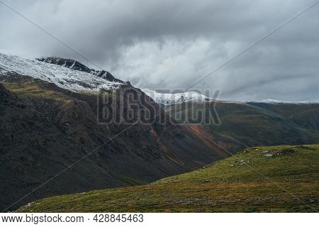Atmospheric Alpine Landscape With Deep Gorge And Snow-capped Multicolor Mountains In Overcast Weathe