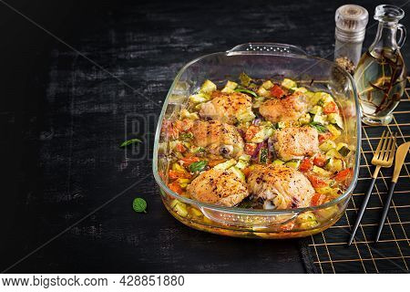 Baked Chicken Thighs, Zucchini And Vegetables In A Baking Dish On A Dark Table.