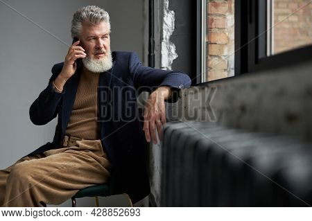 Stylish Gray Haired Middle Aged Man In Casual Wear Looking Out A Window, Making A Call Using Smartph