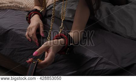 A Girl In Leather Handcuffs And A Collar On A Leash. The Woman On The Bed Holds Out The Leash. The C
