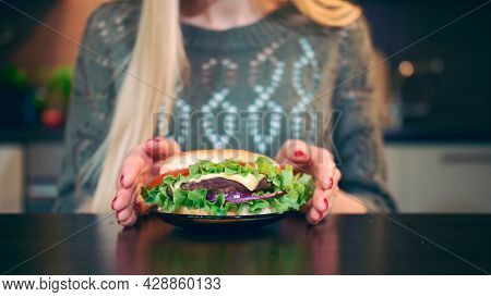Crop View Of Young Lady Preferring Hamburger To Salad. Attractive Young Woman Choosing To Eat Health