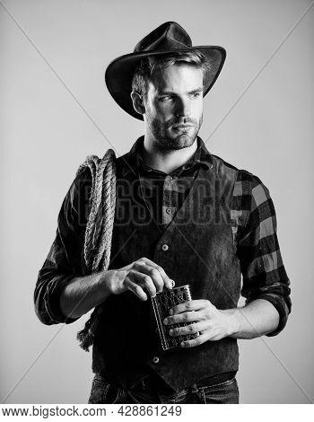 Sheriff Concept. Brutal Cowboy Drinking Alcohol. Man Handsome Cowboy Beige Background. Western Life.