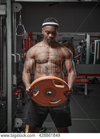 Muscular Athletic African American Guy Exercising With Weight Plate In Gym. Strength Workout Concept