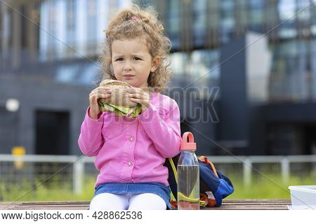 Hungry Beautiful Serious Child With Appetite Eating Fast Food, Drinking Water. Brooding Girl Biting
