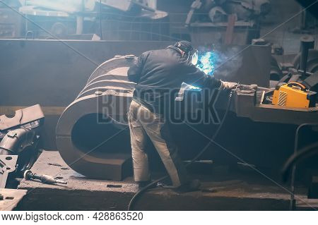 Welder Processes Large Cast Iron Part In Metallurgical Plant After It Has Been Melted Or Manufacture