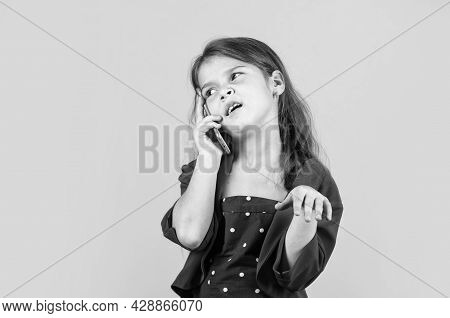 Discussing News. Nice Talk. Happy Childhood. Small Child With Smartphone. Cheerful Little Girl Yello