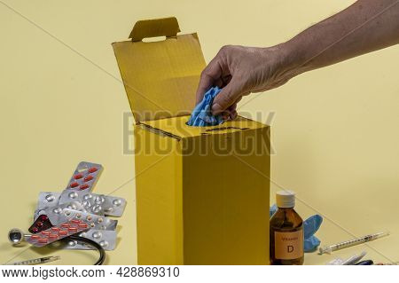 Yellow Disposal Box For Contaminated Or Infectious Products In A Hospital Or Home. Hand Putting A Pr
