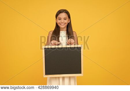 Read This. Something You Need To Know. Happy Smiling Girl Hold Blackboard. Small Kid With Blank Blac