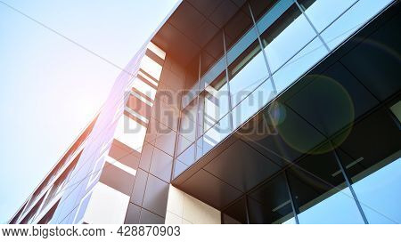 Futuristic Facade Of A Modern Office Building Clad In Glass. Glass Cladding Panels And Windows Of Mo