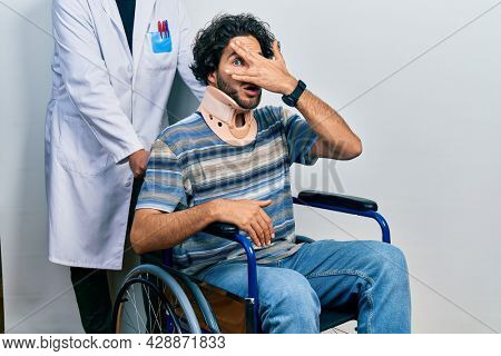Handsome hispanic man sitting on wheelchair wearing neck collar peeking in shock covering face and eyes with hand, looking through fingers with embarrassed expression.
