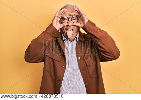 Senior man with grey hair wearing casual jacket and glasses doing ok gesture like binoculars sticking tongue out, eyes looking through fingers. crazy expression.