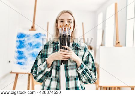 Young artist student girl smiling happy holding paintbrushes covering face at art studio.