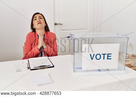 Beautiful middle age hispanic woman at political election sitting by ballot begging and praying with hands together with hope expression on face very emotional and worried. begging.