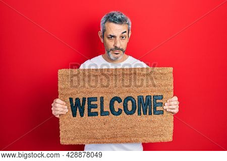 Handsome middle age man with grey hair holding welcome doormat skeptic and nervous, frowning upset because of problem. negative person.