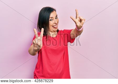 Middle age hispanic woman wearing casual clothes smiling with tongue out showing fingers of both hands doing victory sign. number two.