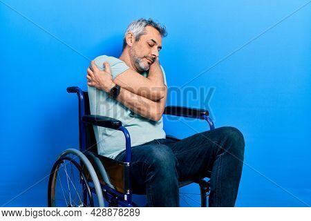 Handsome middle age man with grey hair sitting on wheelchair hugging oneself happy and positive, smiling confident. self love and self care