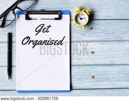 Business Concept. Phrase Get Organised Written On Paper Clipboard  With A Pen,eye Glasses And Alarm